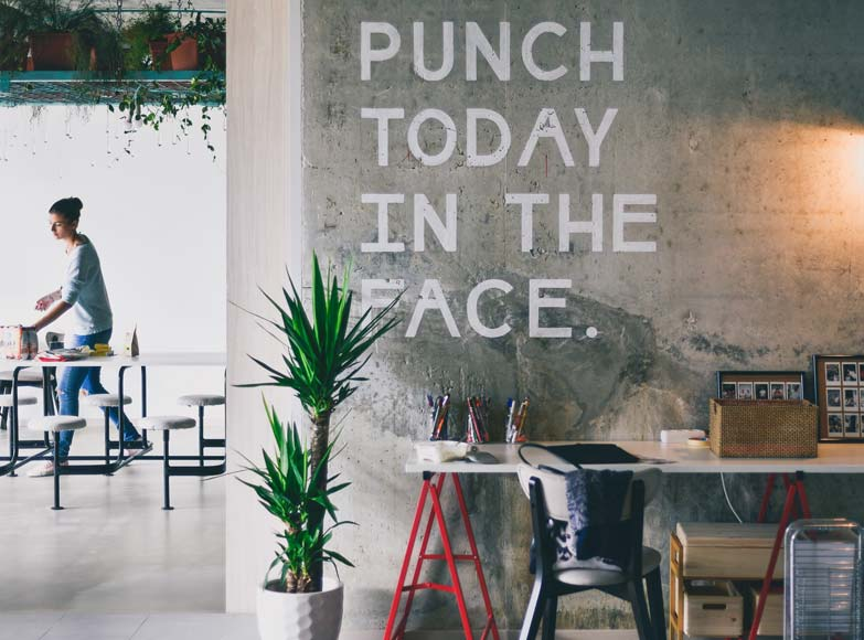 office space with punch today in the face quote on concrete wall