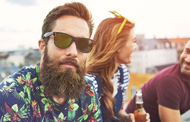 bearded man in tropical shirt with friends drinking