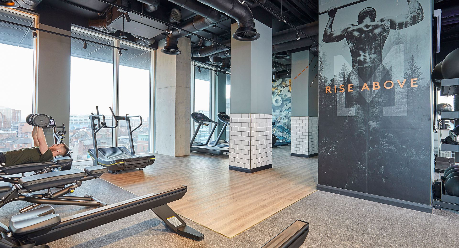urban style gym with gym equipment and graphic wall
