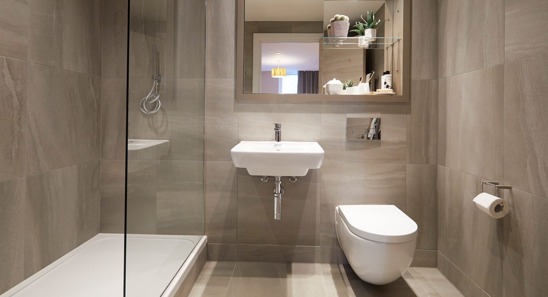 shower room with beige floor to ceiling tiles and chrome fittings