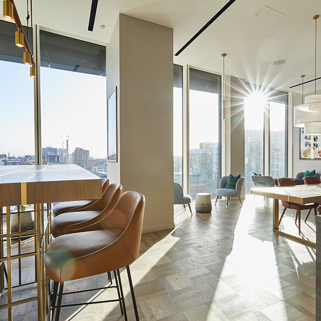 sky lounge with table and chairs and sun shining through floor to ceiling windows