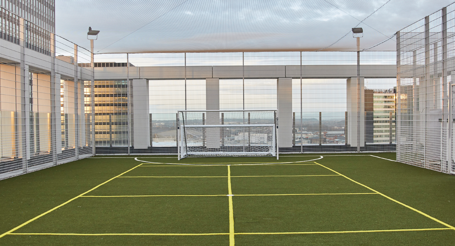 rooftop sports pitch, blue skies and building in background