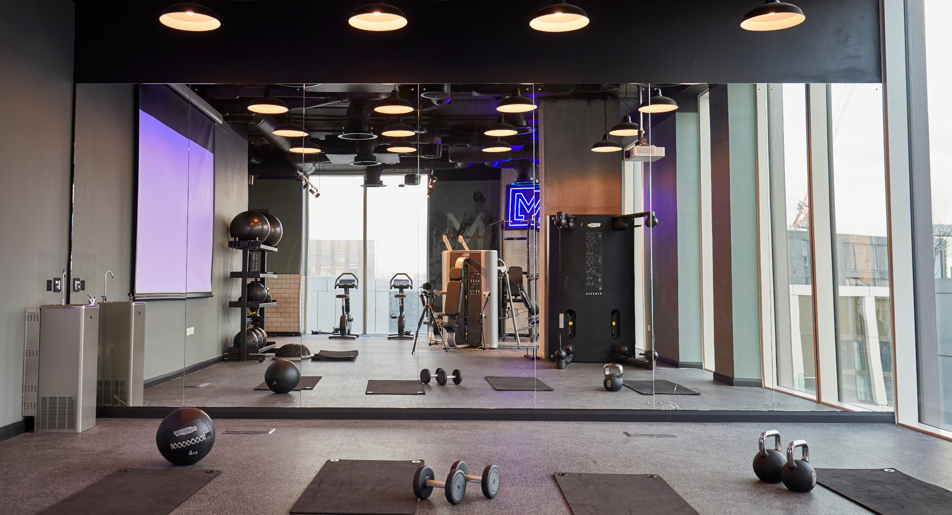 industrial chic gym with studio space, mats, weights and kettlebells