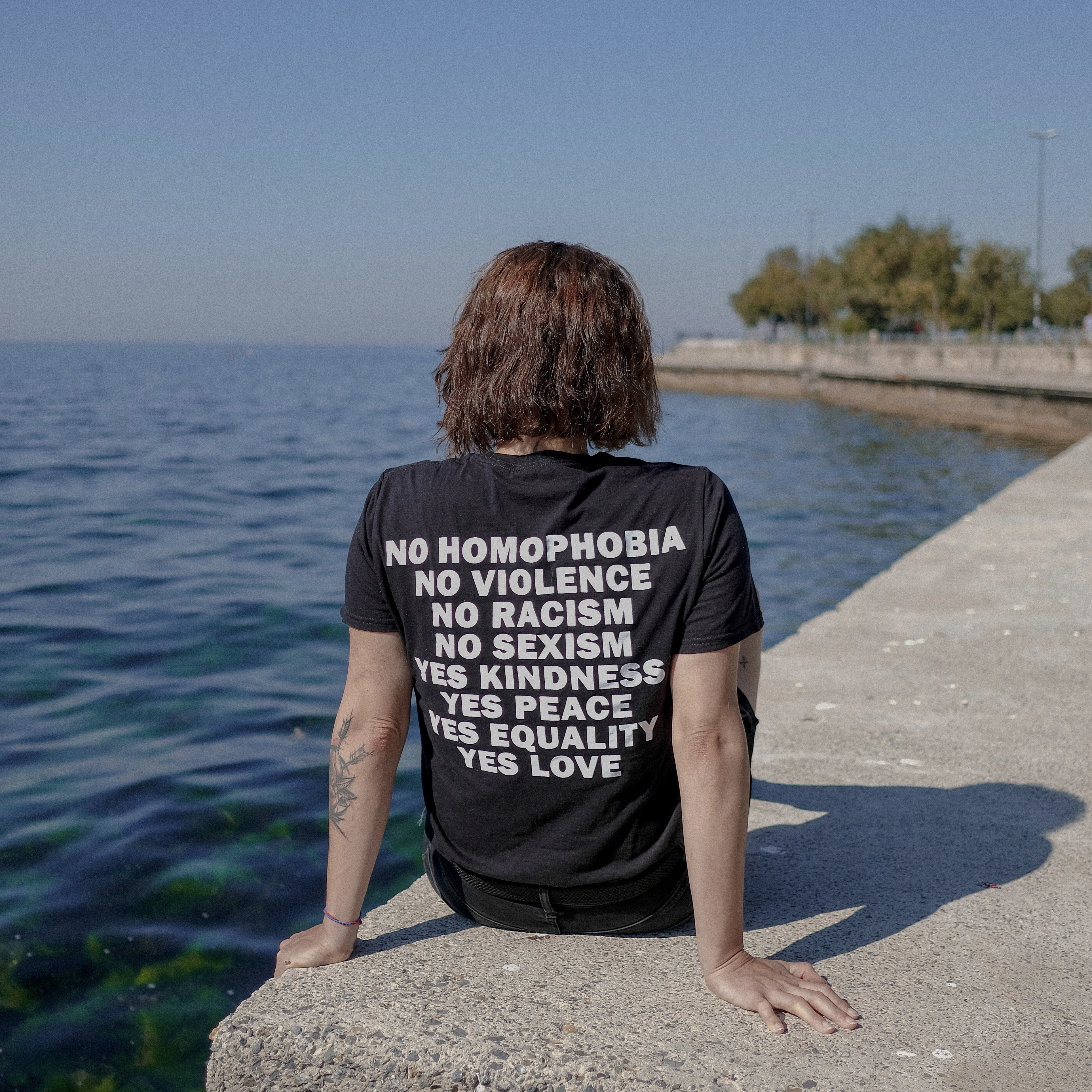 image of someone sat by water with graphic t-shirt on