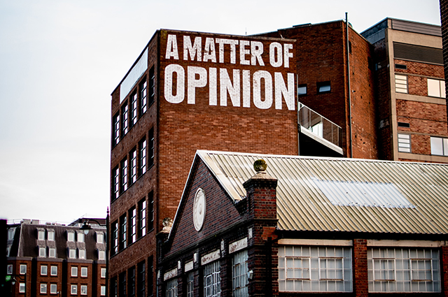 Brick building with the words 'a matter of opinion' painted on the side